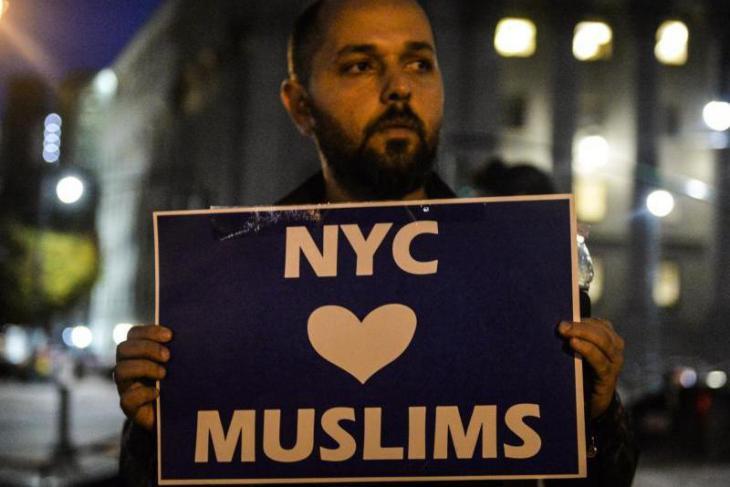 """Muslimischer Mann aus Manhattan hält während einer Nachtwache für die Terroropfer von New York ein Schild mit der Aufschrift """"New York City liebt Muslime"""" hoch; Foto: dpa"""