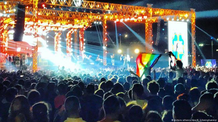 """Bei einem Konzert der libanesischen Popgruppe """"Mashrou' Leila"""" in Kairo wird die Regenbogenflagge geschwenk. Foto: Picture Alliance / dpa"""