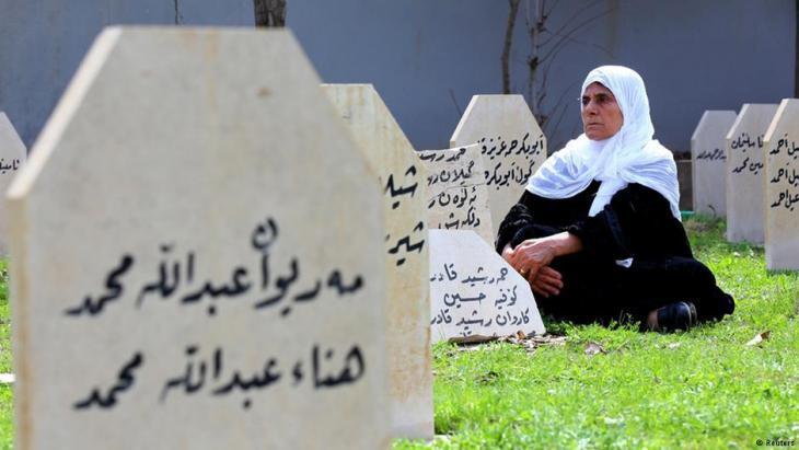 Eine Frau sitzt zwischen den Gräbern auf dem Massenfriedhof für die Halabdscha-Opfer; Foto: Reuters