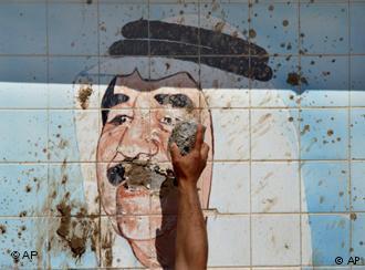 Nach dem Sturz Saddam Husseins zerstört ein Kurde am 10. April 2003 ein Wandbild des Diktators im Nordirak; Foto: AP