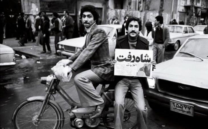 """In Teheran hält ein Fahrradfahrer nach dem Sturz des Schahs einen Zeitungsartikel mit der Überschrift """"Der Schah ist fort""""; Quelle: Iran Journal"""