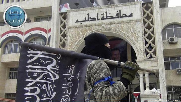 Kämpfer der Al-Nusra-Front vor dem zentralen Verwaltungsgebäude der Provinz Idlib; Foto: AP/picture-alliance