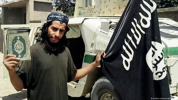 """IS-Terrorist Abdelhamid Abaaoud mit Flagge des """"Islamischen Staates"""" und Koran; Foto: picture-alliance/dpa"""