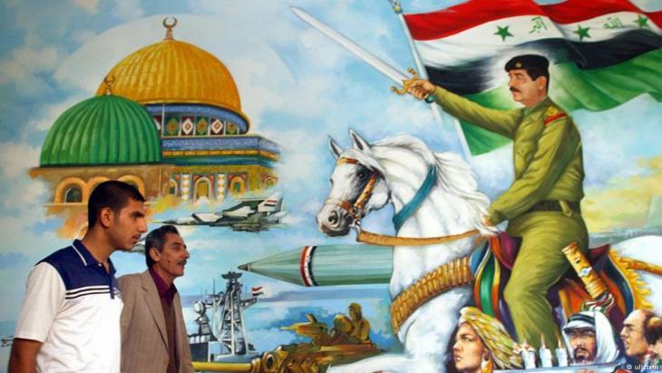 Männer laufen an einem Poster des Saddam Art Center in Bagdad vorbei, das Iraks ehemaligen Staatspräsidenten Saddam Hussein in kriegerischer Pose sowie die Al-Aksa-Moschee in Jerusalem zeigt; Foto: AP