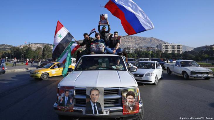 Anhänger Assads schwenken syrische, russische und iranische Fahnen in Damaskus; Foto: picture-alliance/AP