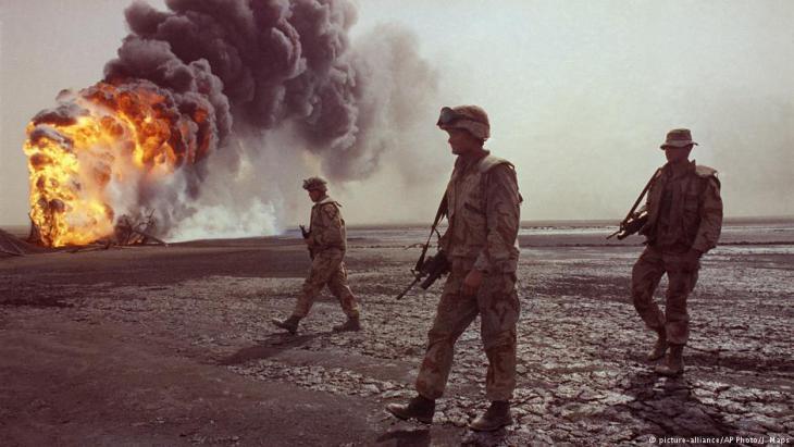 Amerikanische Truppen vor brennenden Ölfeldern vor Kuweit Stadt im Jahr 1991; Foto: