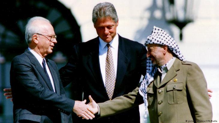Historischer Handschlag: Israels Premierminister Jitzhak Rabin (l) und PLO-Chef Jassir Arafat (r) mit US-Präsident Bill Clinton (m) bei der Unterzeichnung der Osloer Verträge vor dem Weißen Haus in Washington 1993; Foto: picture-alliance/CPA Media