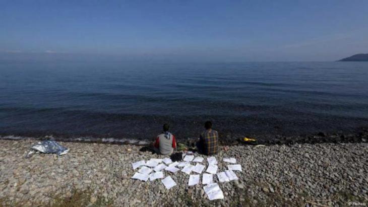 Zwei syrische Flüchtlinge trocknen ihre Dokumente an einem Strand auf der griechischen Insel Lesbos, 19. Oktober 2015 (Foto: Reuters/Yannis Behrakis).