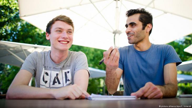 Der deutsche Student Tim Schwarz (links) hilft dem syrischen Flüchtling Renas Ottmann (rechts) beim Erlernen der deutschen Sprache auf dem Gelände der Goethe-Universität in Frankfurt am Main (Foto: picture alliance/dpa/C. Schmidt).