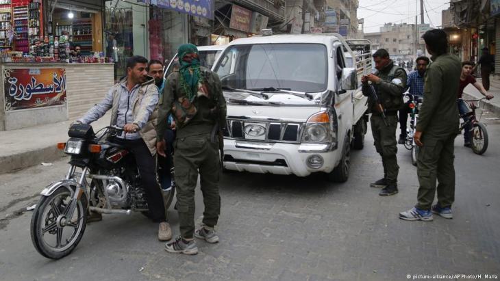 Einheiten der kurdischen YPG kontrollieren Fahrzeuge syrischer Zivilisten in Manbij, Nordsyrien, im März 2018; Foto: picture-alliance/AP/H. Malla