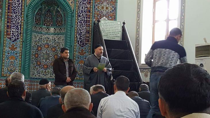 Der Soziologe Javid Shahmaliyev steht während des muslimischen Gebets in einer lokalen Moschee neben dem Imam; Quelle: privat