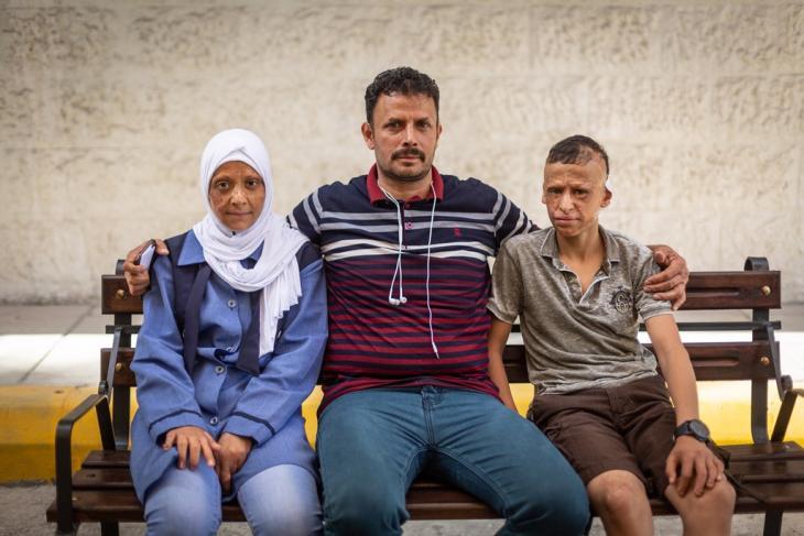 """Die 11-jährige Redha und der 12-jährige Wessam gemeinsam mit ihrem Vater Hasan vor dem """"Mowasah""""-Krankenhaus in Amman; Foto: Philipp Breu"""