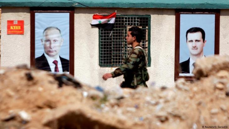 Syrisches Militär vor Putin- und Assad-Porträts in Ost-Ghouta bei Damaskus; Foto: Reuters/Omar Sanadiki