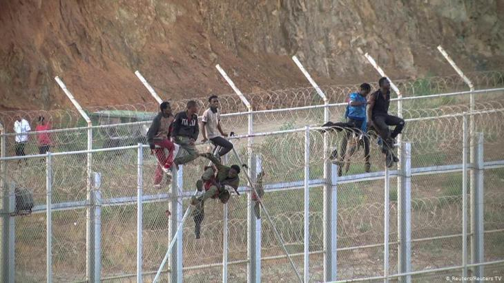 African migrants climb the border fence separating Morocco and Spain's North African enclave of Ceuta (photo: Reuters/Reuters TV)
