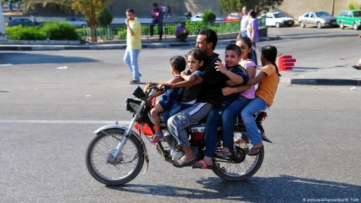 Ein Vater fährt mit seinen fünf Kindern auf einem Motorrad zum Tahrir-Platz in Kairo; Foto: dpa/picture-alliance