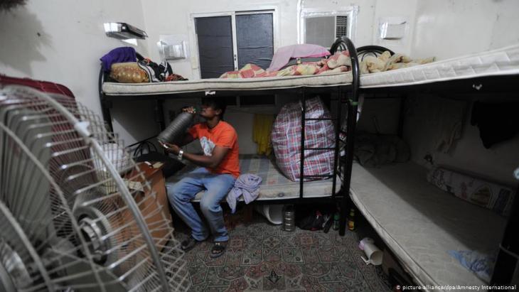 Ein Wanderarbeiter sitzt auf einem Etagenbett in seiner Unterkunft in Qatar; Foto: dpa