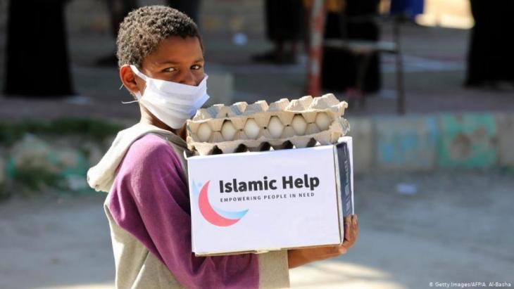 Jemen | Kind mit Mundschutz trägt Hilfsgüter in Taez (Getty Images/AFP/A. Al-Basha)