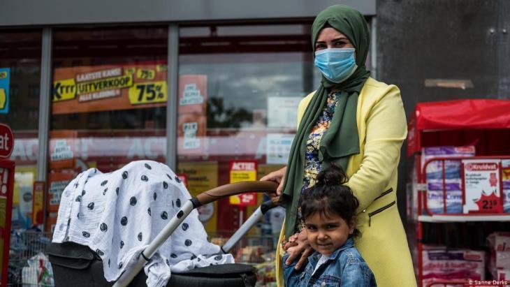 Eine Frau mit Kopftuch und Corona-Maske schiebt ihren Kinderwagen, an der Hand ein weiteres Kind; Foto Sanne Derks
