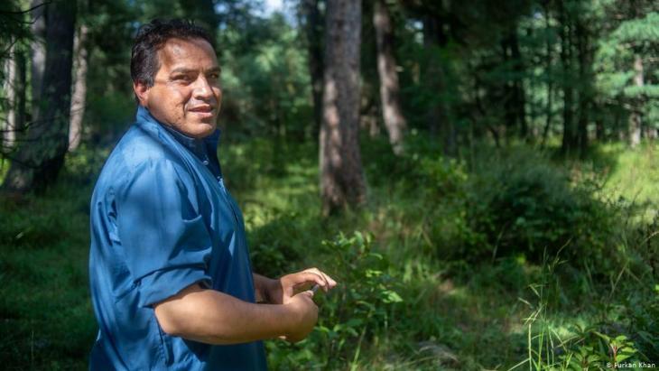 Mushtaq Pahalgami (39) steht vor einem Waldgebiet, das er pflegt; Foto: Furkan Khan