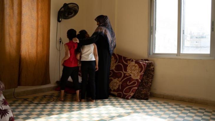 Salha Khalaf Mohamed mit zweien ihrer Kinder im Schlafzimmer: Durch die Explosion wurden die Bettgestelle zerstört, nun schlafen sie auf Matratzen auf dem Boden. Foto: Andrea Backhaus