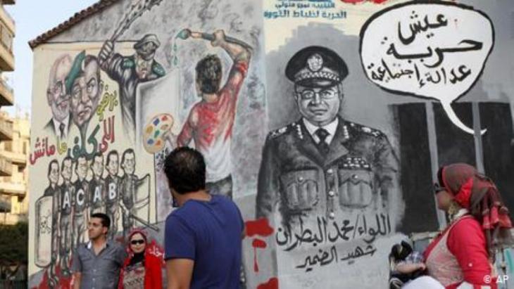 """Herbst 2012: Eine ägyptische Frau trägt ihr Baby an einem Wandbild auf einer kürzlich weiß getünchten Wand vorbei, während andere in der Nähe Fotos machen, Tahrir-Platz, Kairo, Ägypten. Die arabische Schrift in der Gedankenblase lautet: """"Es lebe die Freiheit, soziale Gerechtigkeit! Foto: AP-Foto/Mohammad Hannon"""
