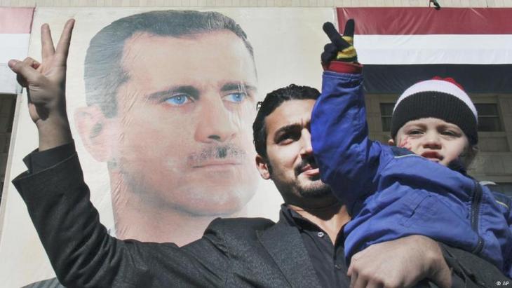 Ein Pro-Regime-Demonstrant hält seinen Sohn hoch während er das Victory-Zeichen vor einem riesigen Porträt des syrischen Präsidenten Bashar Assad zeigt, um seine Solidarität für ihn zu beweisen, Syrien, 20, Januar 2102