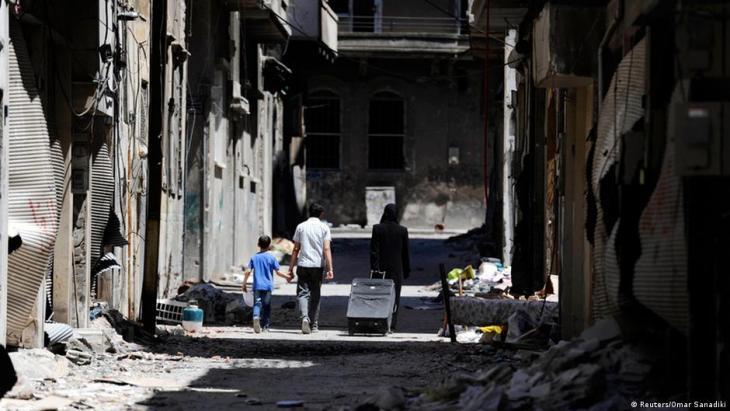 Mitglieder einer Familie laufen vorbei an zerstörten Gebäuden zu ihrem Haus im Wadi Al-Sayeh District im Stadtteil al-Khalidiyeh in Homs, 14 Mai 2014; Foto: Reuters/Omar Sanadiki
