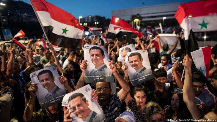 Jubelnde Menschen mit dem Porträt von Staatschef Assad; Foto: Hassan Ammar/AP Photo/picture-alliance