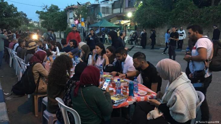 Palästinenser und jüdische Siedler stehen sich während des abendlichen Fastenbrechens gegenüber. (Foto: Tania Kraemer/DW)