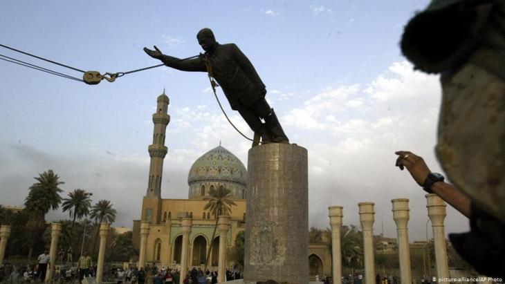 Nach dem Einmarsch der US-Armee im Irak 2003 wird die Statue von Saddam Hussein in Bagdad gestürzt; Foto: picture-alliance/AP Photo