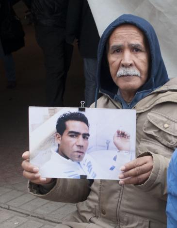 Mohamed hält Plakat mit dem Bild seines getöteten Sohnes während einer Demonstration von Angehörigen der Revolutionsopfer in Tunis hoch; Foto: Sarah Mersch
