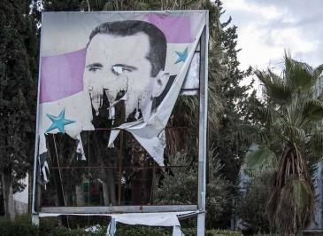 A damaged poster of the Syrian president, Bashar al-Assad, in the northern Syrian city of Aleppo (photo: AP)