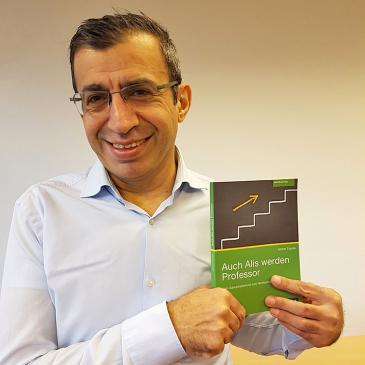"""Prof. Dr. Ahmet Toprak mit seinem Buch """"Auch Alis werden Professor""""; Foto: FH Dortmund"""