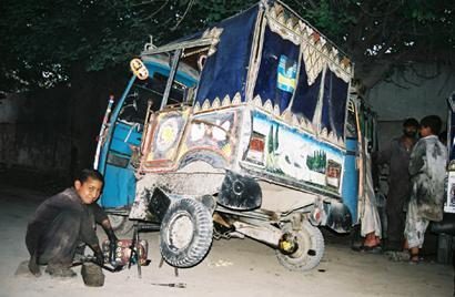 Kind aus Kabul repariert ein Fahrzeug