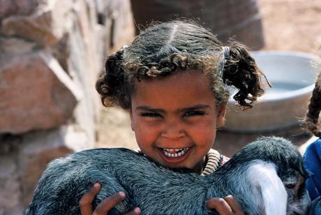Beduinenmädchen spielt mit einer Ziege