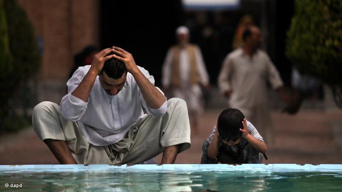 Vater und Sohn im indischen Kaschmir führen die rituelle Reinigung durch, um sich für das Pflichtgebet vorzubereiten. Der Ramadan ist auch eine Zeit des intensiven Gebets und der inneren Einkehr; Foto: dapd