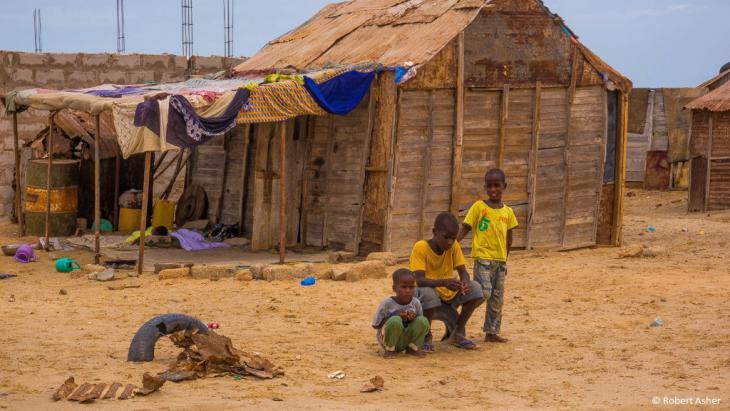 Jungen vor einem notdürftig zusammengezimmerten Haus