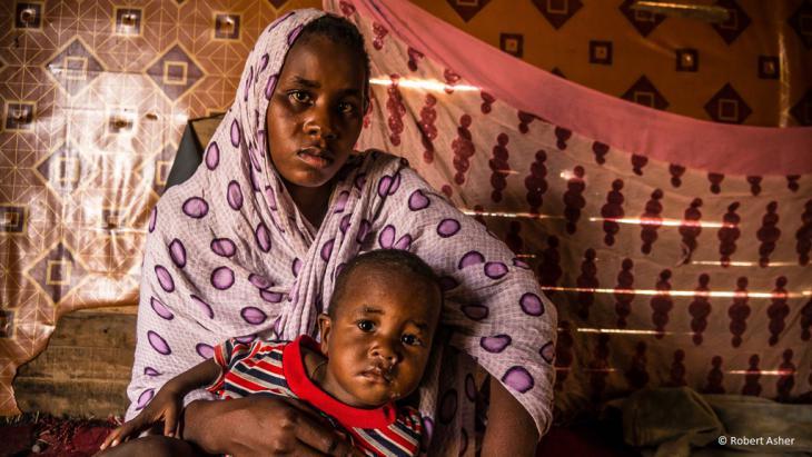 In einen gepunkteten Schal gehüllt, hält Mbarka ihren kleinen Sohn in den Armen.