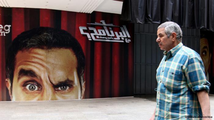 Mann in Kairo passiert Werbeplakat des Satirikers Bassem Youssef; Foto: dpa/picture-alliance