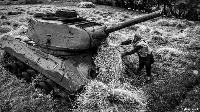 Ein afghanischer Bauer lädt seine Ernte auf einen noch aus der sowjetischen Besatzungszeit stammenden Panzer; Foto: Majid Saeedi