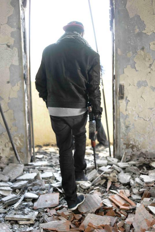 Junger Stammeskämpfer begutachtet in Warschefana zerstörtes Gebäude; Foto: Valerie Stocker