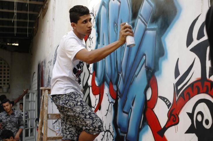 Junger Graffiti-Künstler vor seinem Wandgemälde an einer zerbombten libyschen Militärbasis; Foto: Valerie Stocker