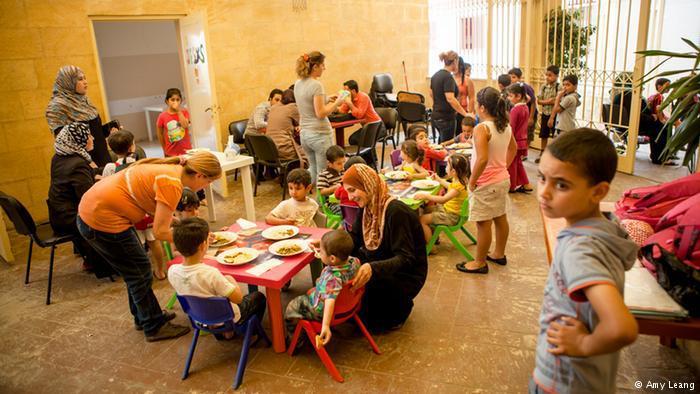 Syrische Schüler beim Mittagessen in einem Hof; Foto: Amy Leang
