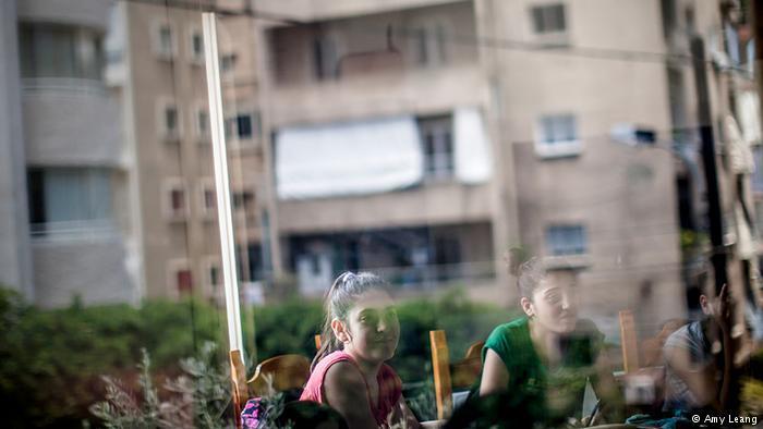 Die Wohnhäuser der Schüler spiegeln sich in den Fensterscheiben der Schule. Viele sehen die Schule als zweites Zuhause; Foto: Amy Leang