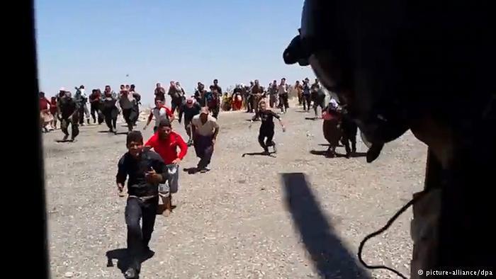Flüchtlinge kommen dem Helikopter entgegen, um Hilfsgüter in Empfang zu nehmen; Foto: picture-alliance/dpa