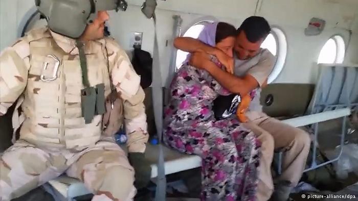 Eine jesidische Frau und ein jesidischer Mann werden in einem Hubschrauber in Sicherheit gebracht; Foto: picture-alliance/dpa