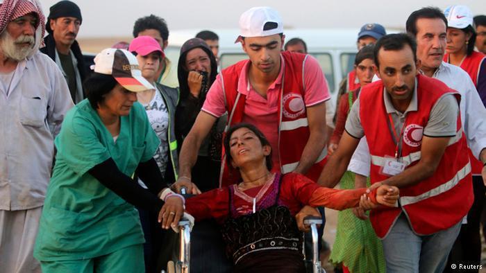 Mitarbeiter des Roten Halbmondes helfen einer jesidischen Frau: Foto: Reuters