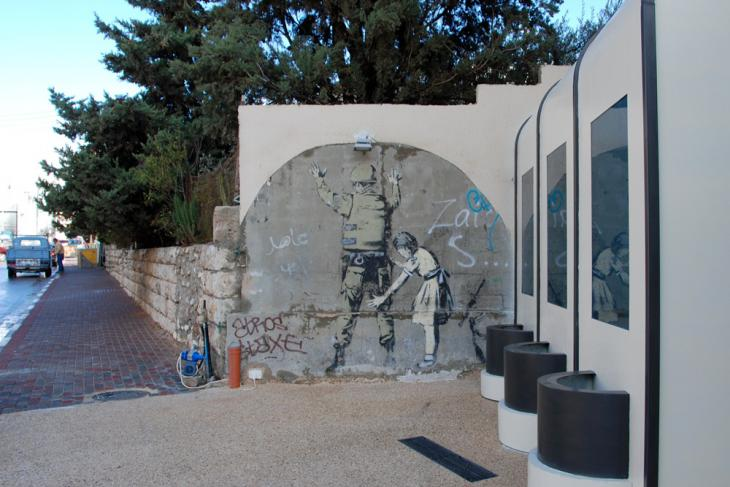Ein israelischer Soldat wird von einem jungen Mädchen abgetatstet - Graffiti von Bansky aus dem Jahr 2007; Foto: Laura Overmeyer
