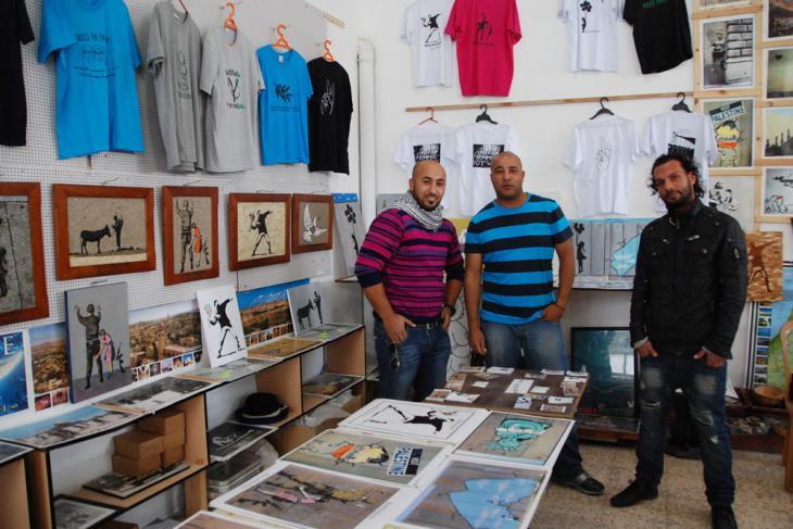 """Yamen Elabed (Mitte) gemeinsam mit zwei Kollegen in seinem Souvenir-Laden """"Banksy's Shop"""" in Bethlehem; Foto: Laura Overmeyer"""