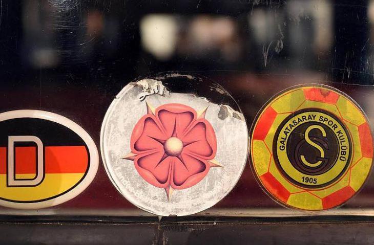 """Ein """"D Schild"""" (l) und der Aufkleber eines Türkischen Fußballvereins (r) im Haus der Geschichte; Foto: dpa/Henning Kaiser"""